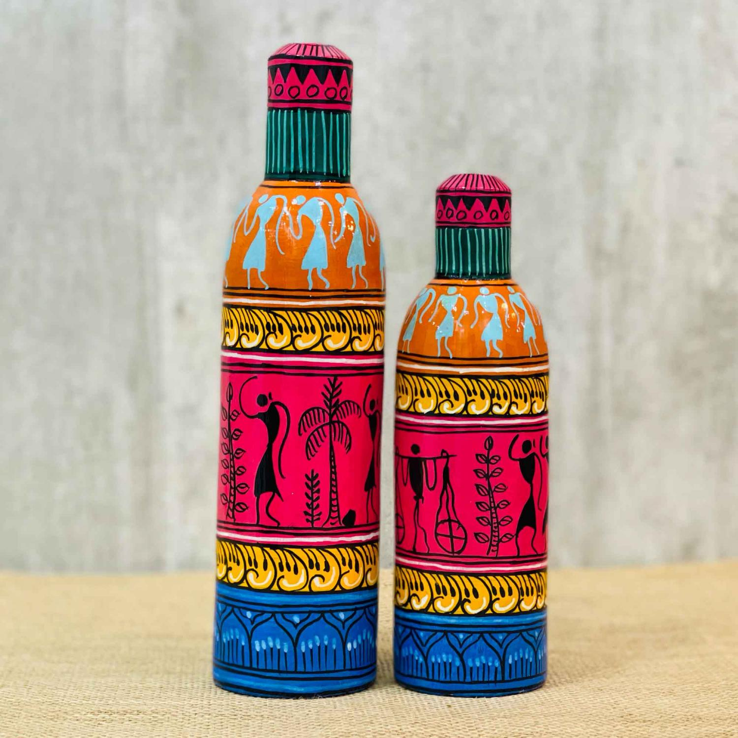 Decorative bottles with tribal motifs in green, pink, mustard and orange colors with a blue base on a table with a beige table cloth and a grey background