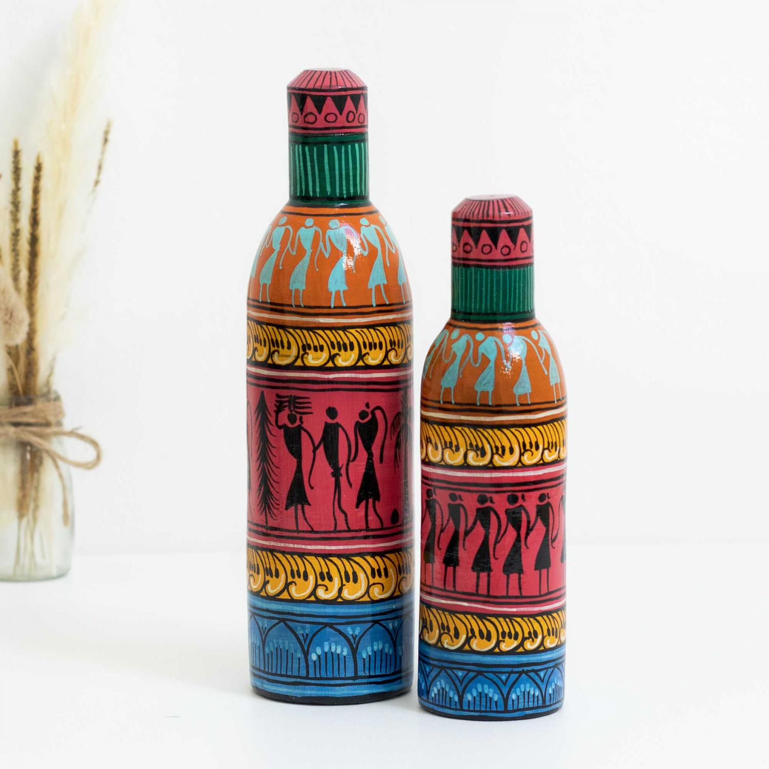 Decorative bottles with tribal motifs in green, pink, mustard and orange colors with a blue base on a white table with dried pampas grass to the left in the background