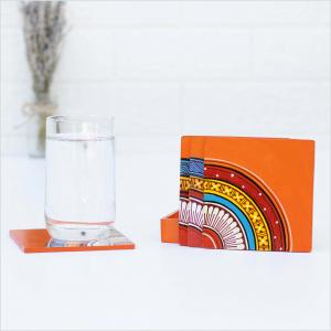 Orange coasters with red, yellow and blue motifs standing in front of an orange holder on a white surface next to a glass of water standing on a coaster and a vase of dried flowers in the background
