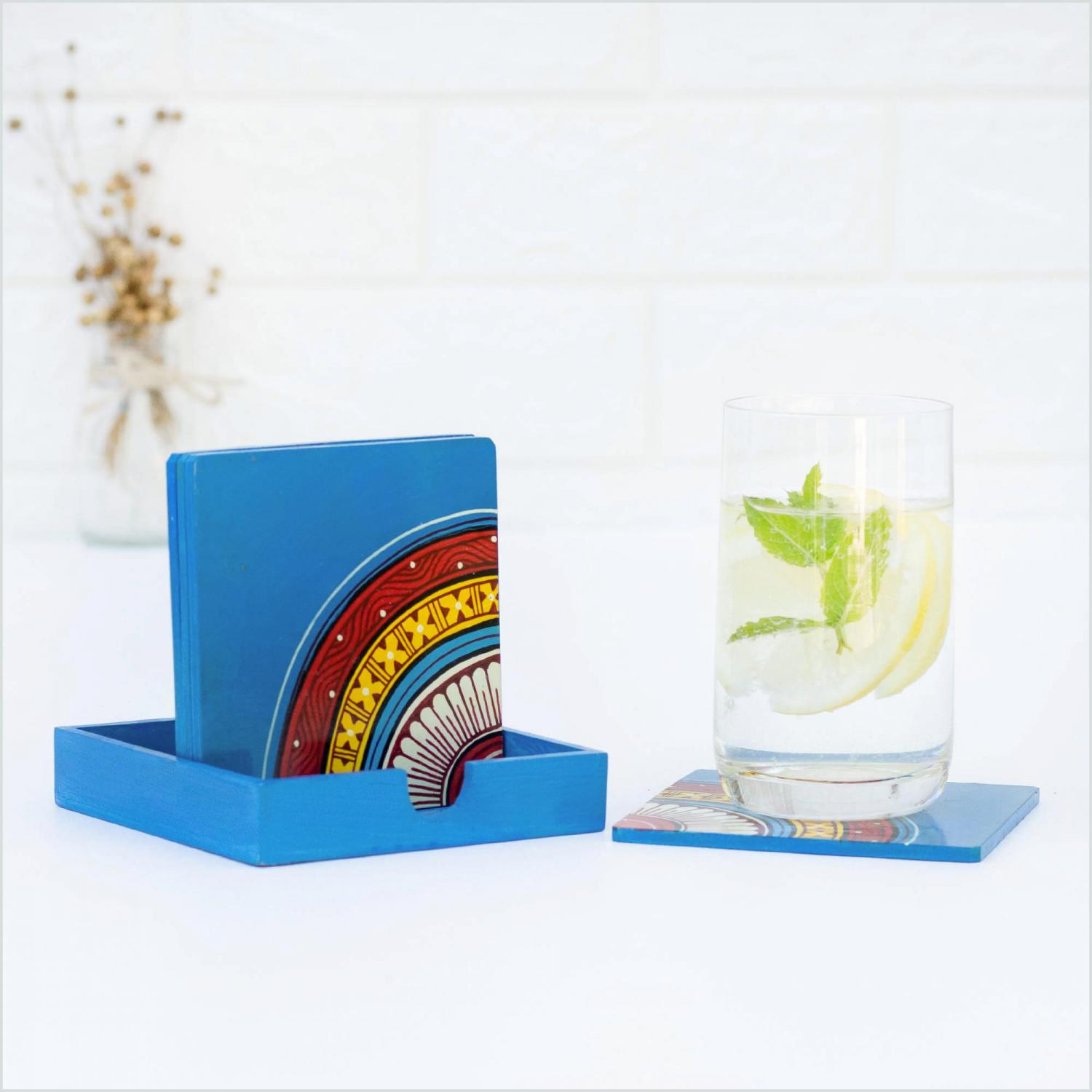 Blue coasters with red, yellow and blue motifs standing on a blue holder on a white surface next to a glass of water with mint and lemon standing on a coaster and a vase of dried flowers in the background