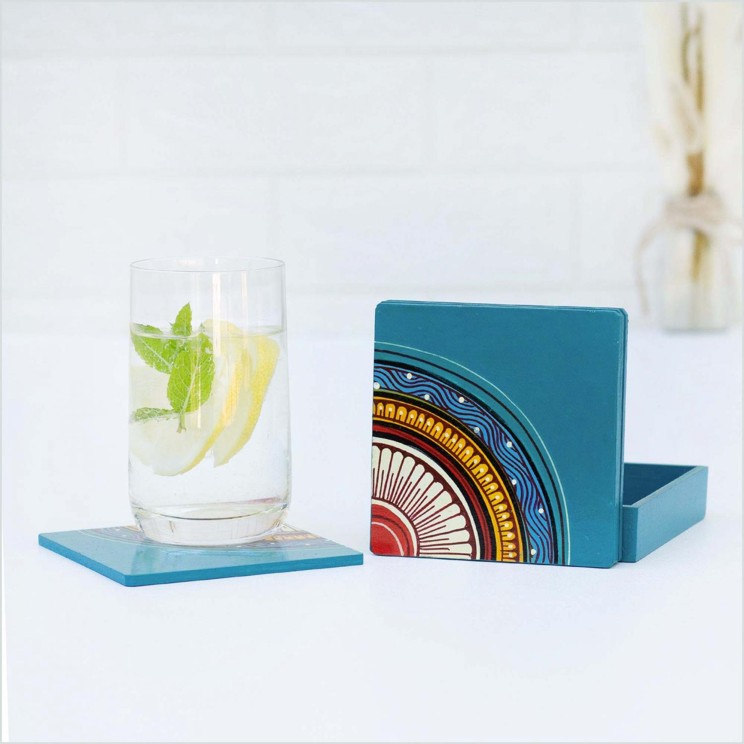 Blue coasters with red, yellow and blue motifs standing in front of a blue holder on a white surface next to a glass of water with mint and lemon standing on a coaster and a vase of dried flowers in the background