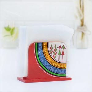 Red napkin holder with green, blue and yellow tribal motifs holding white napkins placed on a white surface with a vase with dried flowers and a glass of water with green leaves in the background