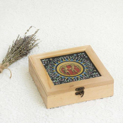 Jewelry box in beige and black with tribal motifs in the center placed next to dried lavender on a white background