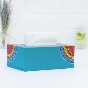 Blue napkin holder with yellow, red and blue motifs holding white napkins and standing on a white surface with a vase with dried lavender, a glass with green leaves and a white wall in the background