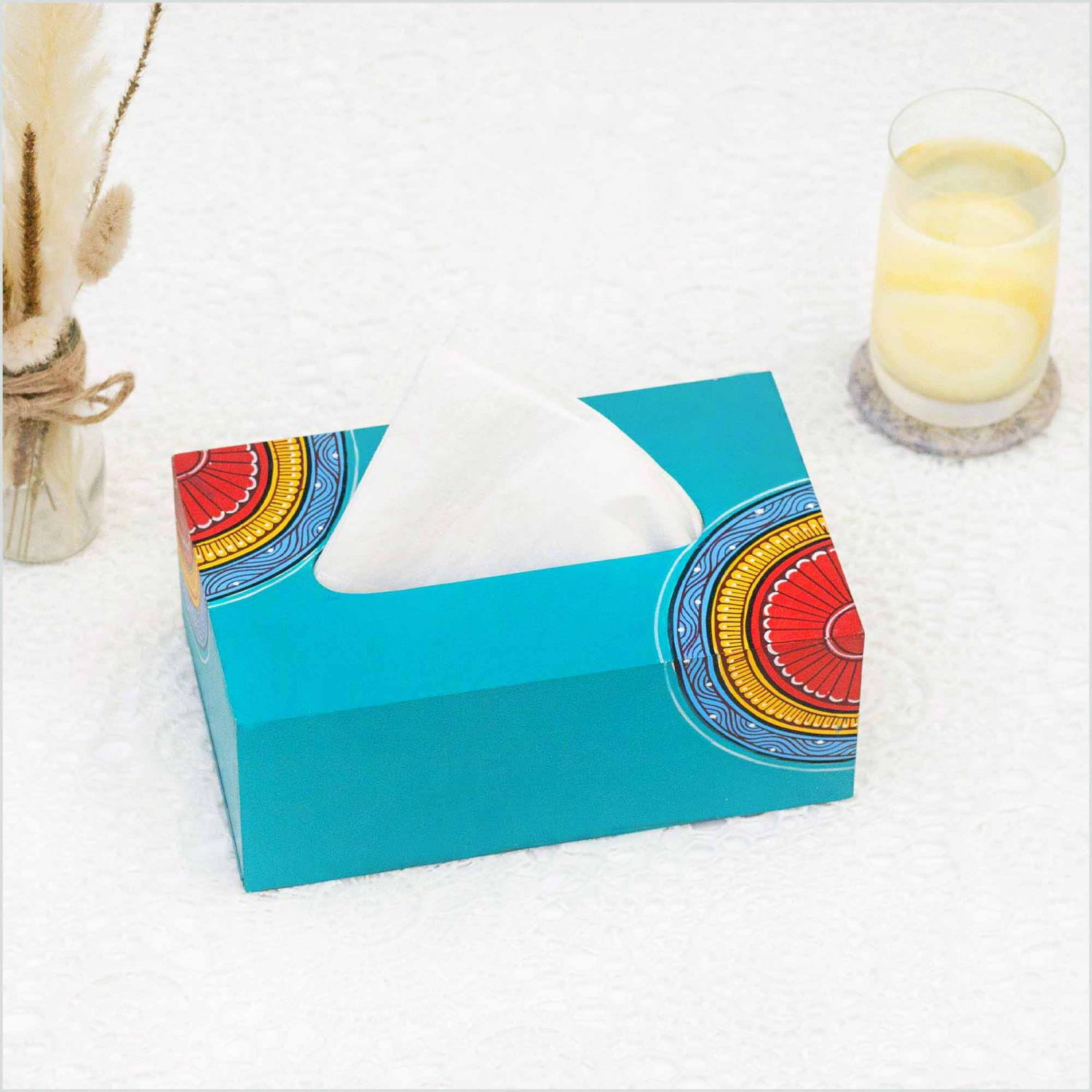 Blue napkin holder with yellow, red and blue motifs holding white napkins and standing on a white surface with a vase with dried oats, a glass of lemonade and a white wall in the background