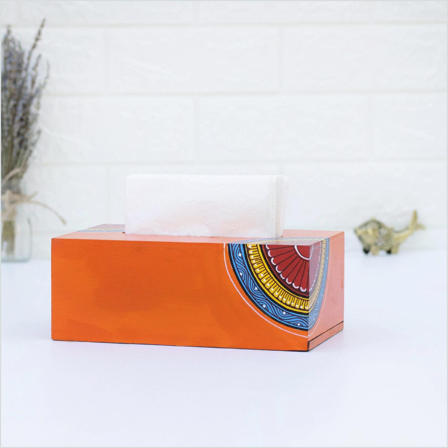 Orange napkin holder with blue, yellow and red motifs holding white napkins and standing on a white surface with a brass figurine, a vase with dried lavender and a white wall in the background