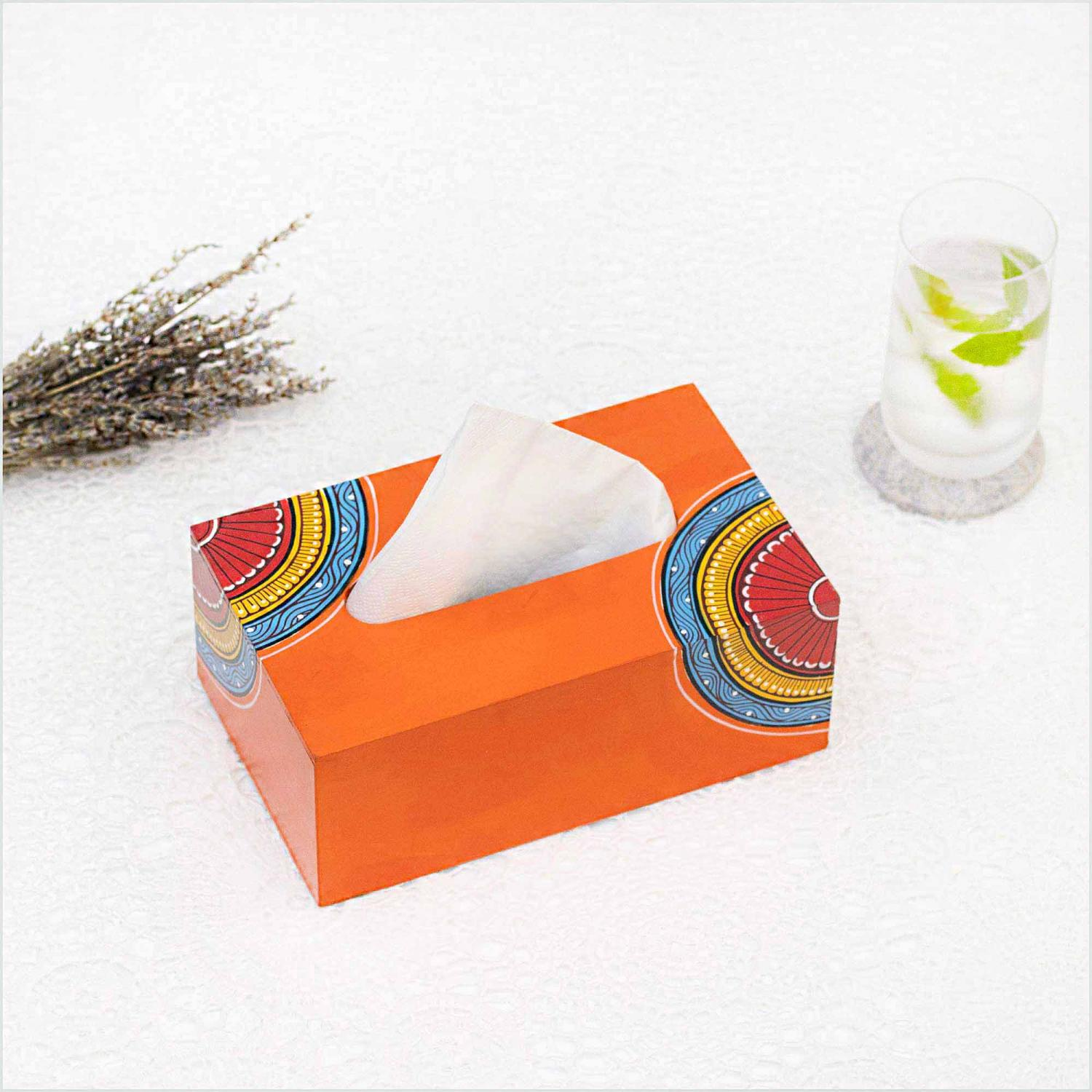 Orange napkin holder with blue, yellow and red motifs holding white napkins and standing on a white surface with a glass with green leaves in the right and a dried lavender in the left and a white wall in the background