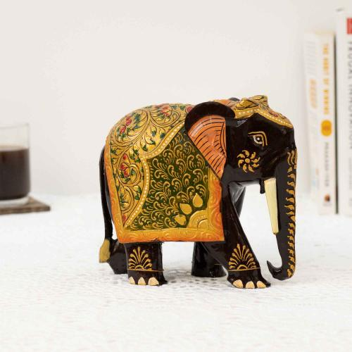 Elephant figurine in black painted with a mix of colors placed on a white surface with a collection of books and a cup of coffee placed on a coaster in the background.