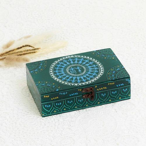 Green jewelry box printed in tribal motifs with a sun shaped design at the top of the box placed next to dried flowers on a white background