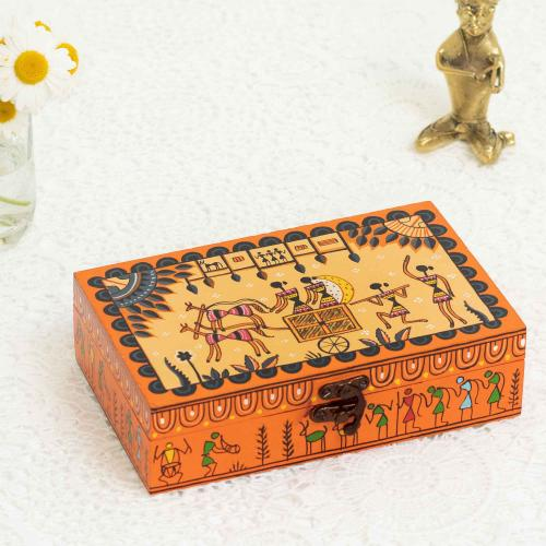 Jewelry box with orange color and tribal prints placed next to a brass figurine and a vase with daisies on a white background