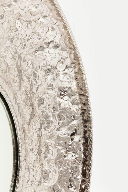 En silverfärgad spegelram med ornament.