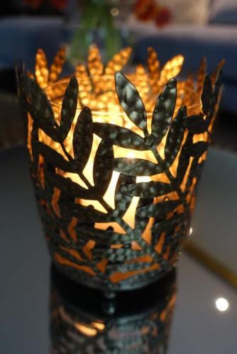 Dekorativ ljuslykta med lövmönster i ärgad mässingsfinish