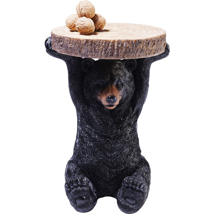Sidobord björn sitter med ramarna uppsträckta och håller bordsskivan i form av ett avsågat träd med bark på sidan och ådringen på ovansidan.