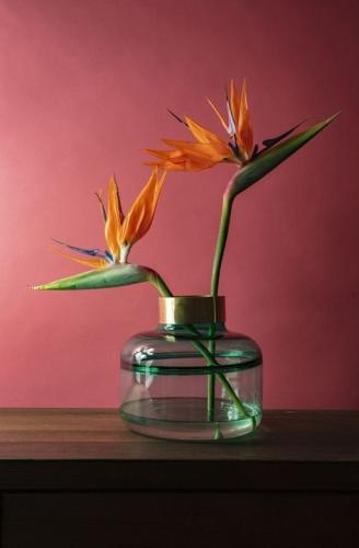 En vacker rund vas i klart grönt glas och dekorativ kant i mässing