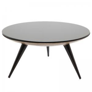 Ett formstarkt runt soffbord med högblank svart glasskiva