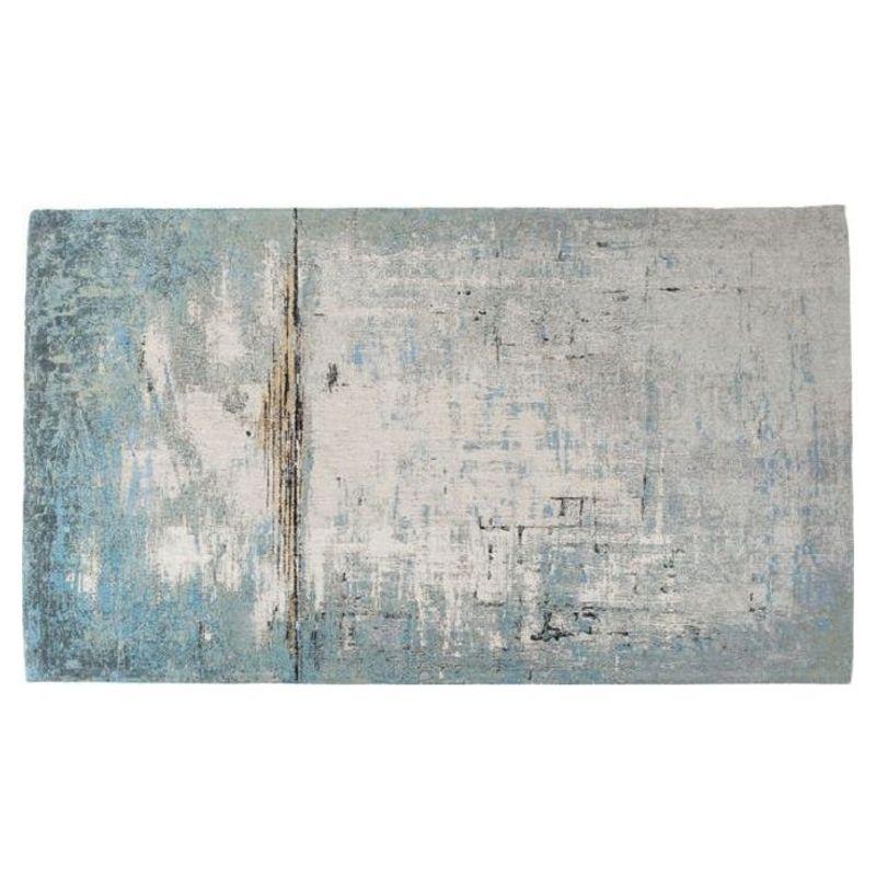 En stor fin matta med diskret mönster i grå, blå och beigea nyanser.