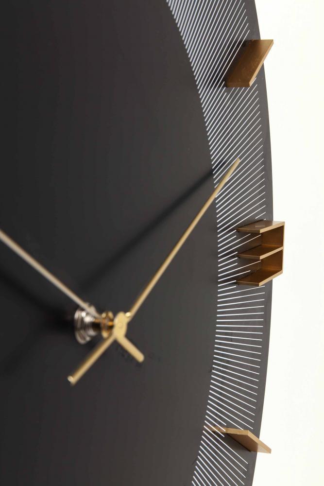 En stilren, modern svart klocka med siffror och visare i mässing