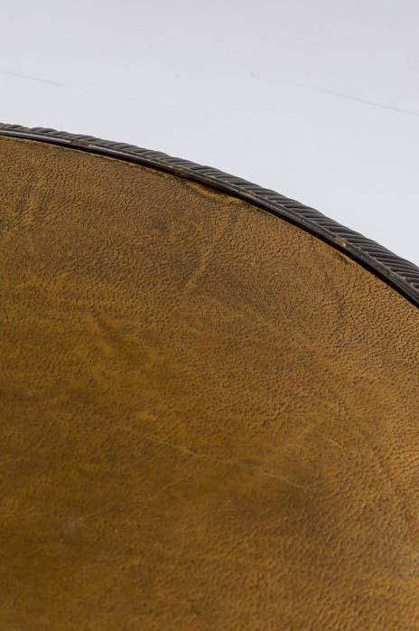 Ett runt lågt soffbord med bordskiva i ärgad bronsfinish